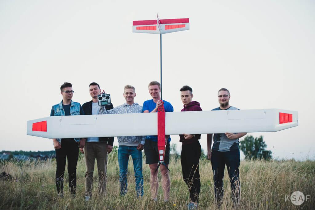 Czterech studentów trzyma samolot solar plane, stoją na łące na tle drzew