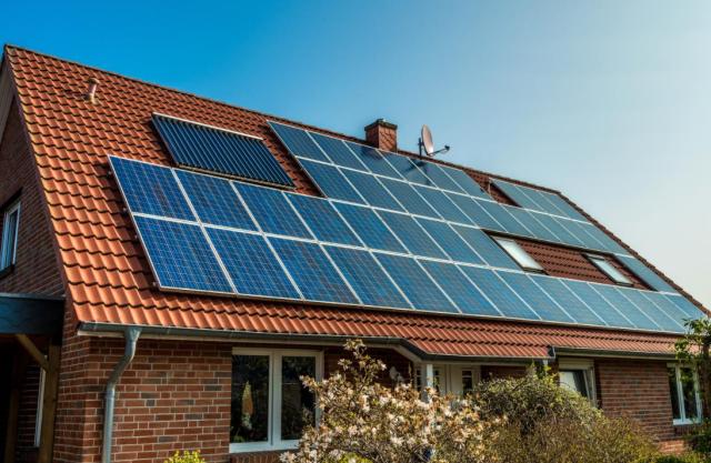 Panele fotowoltaiczne czy kolektory słoneczne? Oba rodzaje są widoczne na dachu domu z cegły