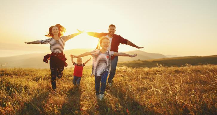 karta dużej rodziny - rodzina biegnąca po polu przy zachodzie słońca