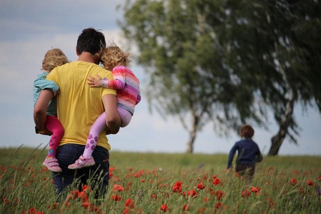 tata na polu z trójką dzieci